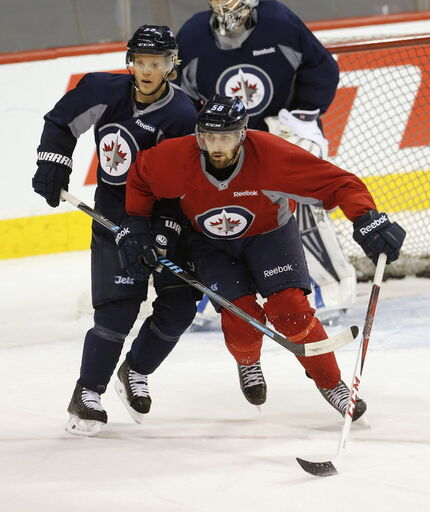 Winnipeg Jets centre Eric O'Dell #58 works against defence #39 Tobi Enstrom during practice in this file photo from April.
