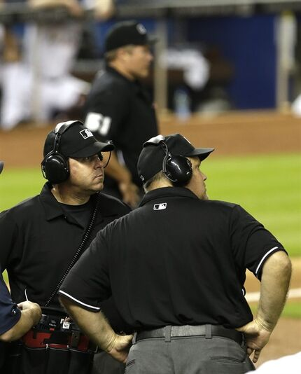 ADVANCE FOR WEEKEND EDITIONS, AUG. 30-31 - In this May 23, 2014, file photo,First base umpire Doug Eddings, left foreground, and second base umpire Brian O'Nora, right, watch a replay on the giant screen during a baseball game between the Milwaukee Brewers and the Miami Marlins in Miami. There were more than 1,000 challenges so far in this new era of replay, and it's only August. Now get ready for an even longer postseason parade of those slow strolls, when a ruling could really be the difference between a World Series winner and an early exit. (AP Photo/Alan Diaz, File)