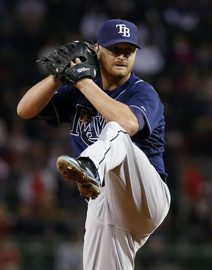 Tampa Bay Rays starting pitcher Alex Cobb winds up during the first inning of a baseball game against the Boston Red Sox at Fenway Park in Boston, Tuesday, Sept. 23, 2014. (AP Photo/Elise Amendola)