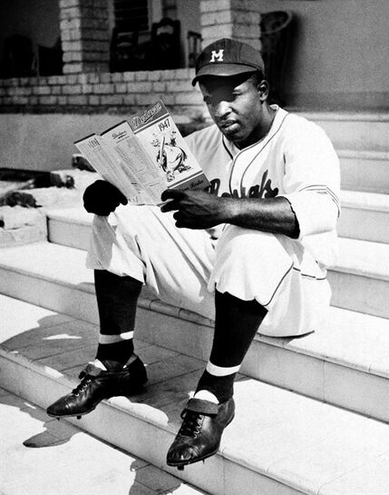 FILE - In this Feb. 27, 1947 file photo, Jackie Robinson, of the Montreal Royals, looks at a roster of the Brooklyn Dodgers in Havana, Cuba, where he's training with the Royals, a Brooklyn Dodger farm club. It was during spring training in 1947 in Havana that the Brooklyn Dodgers got an extended look at Montreal Royals star Jackie Robinson, who later that year became the first African-American player in the majors. The Wednesday, Dec. 17, 2014 announcement that the U.S. plans to restore diplomatic ties with the Caribbean nation could usher in a new era in U.S.-Cuba baseball relations, which were strained after the Castro revolution and the U.S.-led economic embargo. (AP Photo, File)
