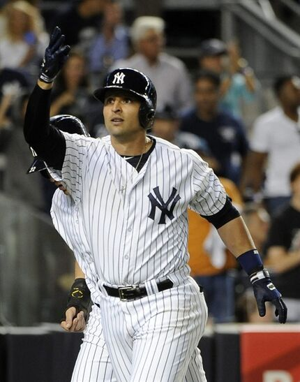 FILE - In this Aug. 22, 2014, file photo, New York Yankees' Martin Prado throws a kiss to fans after he hit a two-run home run off Chicago White Sox starting pitcher John Danks in the third inning of a baseball game at Yankee Stadium in New York. The Yankees have acquired pitcher Nathan Eovaldi, outfielder Garrett Jones and minor league pitcher Domingo German from the Marlins for versatile Martin Prado and pitcher David Phelps, Friday, Dec. 19, 2014. (AP Photo/Kathy Kmonicek, File)