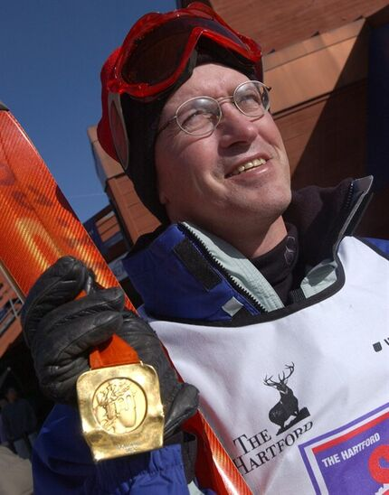 FILE - In this Dec. 11, 2002, file photo, 1984 Olympic downhill skiing gold medalist Bill Johnson shows off his medal while eyeing the ski slopes in Breckenridge, Colo. Most days are a struggle for Olympic downhill champion Bill Johnson as he lies in bed at an assisted living facility in Gresham, Oregon, watching his favorite television shows. He can't move his legs and arms anymore. He can barely speak. But this brought a smile to Johnson's face: On his 55th birthday Monday, March 30, 2015, U.S. Ski Team sent him a video tribute, with downhiller Steven Nyman telling him,