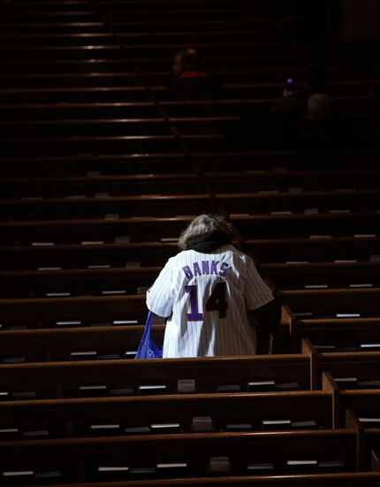 Trudie Acheatel, wearing an Ernie Banks jersey, finds a seat in the church after paying her respects to the Chicago Cubs' Hall of Famer who died after a heart attack last week, during a public visitation Friday, Jan. 30, 2015, in Chicago.