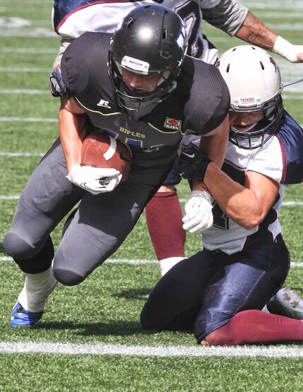 The Winnipeg Rifles' Niclas Bembenek scores a touchdown despite being pulled down by the Regina Thunders' Dustin Erbach in the second quarter of a Prairie Conference junior footbal game at Investors Group Field Sunday afternoon.