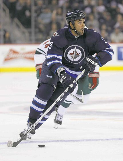 Winnipeg Jets Dustin Byfuglien (33) carries the puck into the Minnesota Wild's zone during second period pre-season NHL hockey action in Winnipeg, Monday, September 22, 2014. THE CANADIAN PRESS/Trevor Hagan