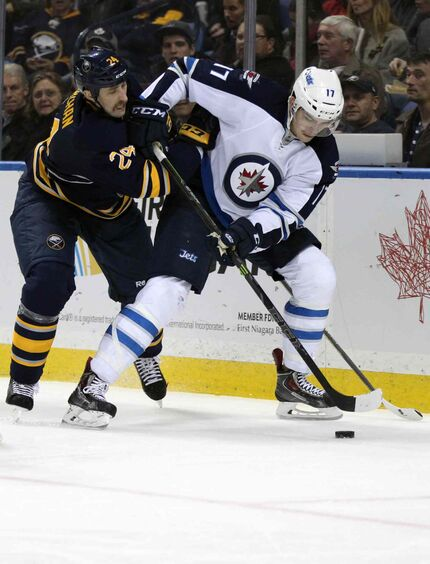 Buffalo Sabres defenseman Tyson Strachan (24) battles for the puck with Winnipeg Jets left winger Adam Lowry (17) during the second period of an NHL hockey game Wednesday, Nov. 26, 2014, in Buffalo, N.Y.