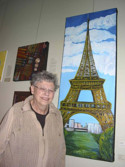 Bev Morton, the owner and manager of the Wayne Arthur Gallery in St. Boniface, stands by Eileen Kaspick's painting titled Eiffel Tower.