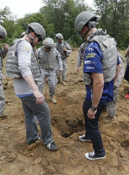 IndyCar driver�Graham Rahal�and NASCAR driver�Dale Earnhardt Jr. helps soldiers cover an explosive, at Camp Atterbury Wednesday, July 23, 2014, in Edinburgh, Ind. (AP Photo/Darron Cummings)