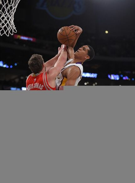 Los Angeles Lakers guard Jordan Clarkson, right, goes up for a shot as Houston Rockets forward Donatas Motiejunas, of Lithuania, defends during the first half of an NBA basketball game, Sunday, Jan. 25, 2015, in Los Angeles. (AP Photo/Mark J. Terrill)
