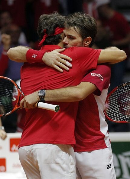 Switzerland's Roger Federer hugs compatriot Stanislas Wawrinka, right, after defeating French pair Julien Benneteau and Richard Gasquet in their doubles match for the Davis Cup final in Lille, northern France, Saturday, Nov.22, 2014. Switzerland leads France 2-1.(AP Photo/Christophe Ena)