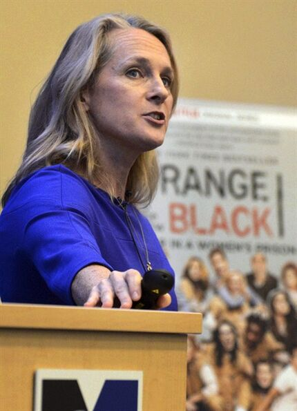 In this photo taken on Tuesday, Sept. 30, 2014, and released by the University of Massachusetts-Lowell, author Piper Kerman talks about her memoir,