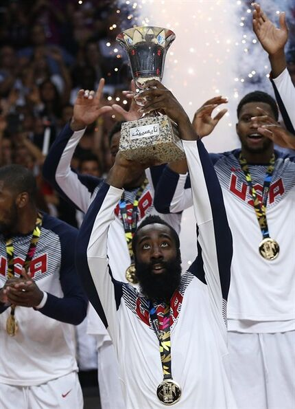 United States' James Harden holds the trophy as he celebrates with teammates after winning the final World Basketball match between the United States and Serbia at the Palacio de los Deportes stadium in Madrid, Spain, Sunday, Sept. 14, 2014. (AP Photo/Daniel Ochoa de Olza)