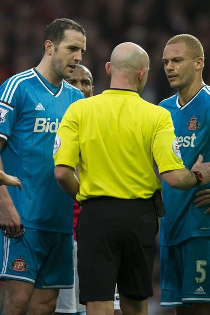 Sunderland's John O'Shea, left, and Wes Brown remonstrate with referee Roger East after the latter is mistakenly sent off for the foul on Manchester United's Radamel Falcao during the English Premier League soccer match between Manchester United and Sunderland at Old Trafford Stadium, Manchester, England, Saturday Feb. 28, 2015. (AP Photo/Jon Super)