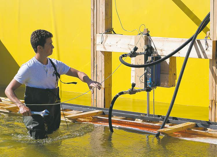 DAVID LIPNOWSKI / WINNIPEG FREE PRESSU of M engineering student Steven Harms adjusts the wave pool, which mimics flood conditions and tests flood-control devices.