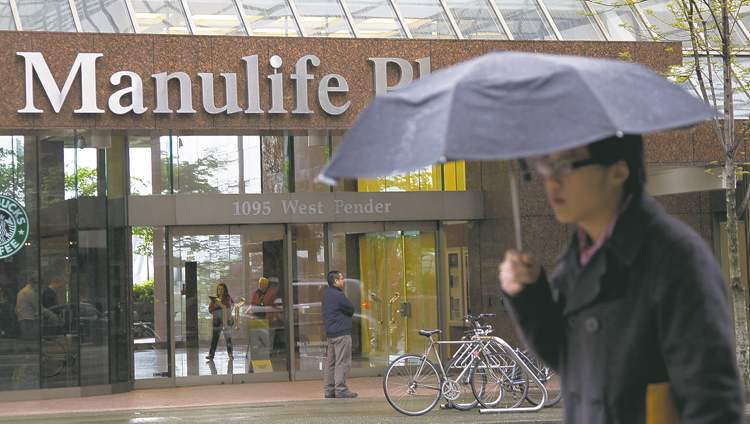 A pedestrian walks past the Manulife building in downtown Vancouver, B.C.