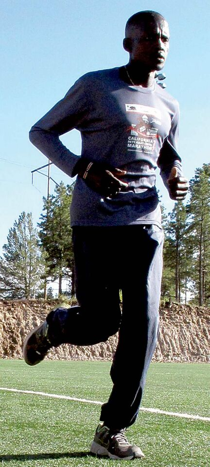 In a Wednesday, Aug. 1, 2012, photo, Guor Marial, 28, jogs around a soccer field in Flagstaff, Ariz. The Sudanese refugee learned just weeks ago that he could compete in the men's marathon at the Olympics as an independent athlete. (AP Photo/Felicia Fonseca)