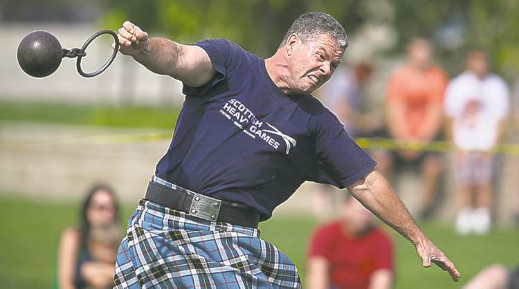 Dean Richards throws the light weight (28 pounds) for distance during a display of Highland Games activities at The Forks Sunday.