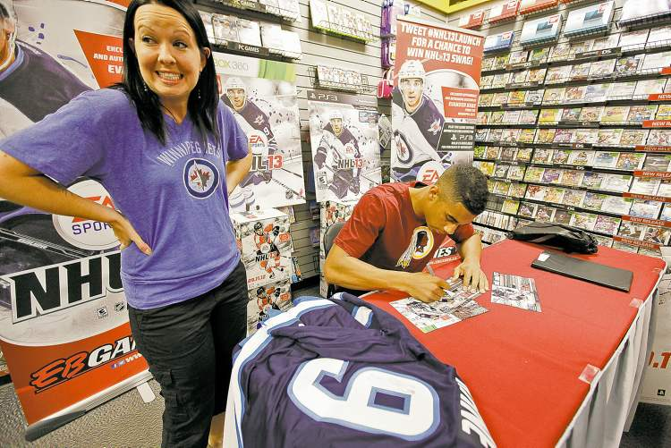 Jets winger Evander Kane signs a poster for Victoria Zachanowich prior to the release of NHL 13 at EB Games in Winnipeg on Monday.