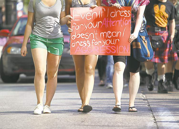 Women carry signs at Saturday's SlutWalk.