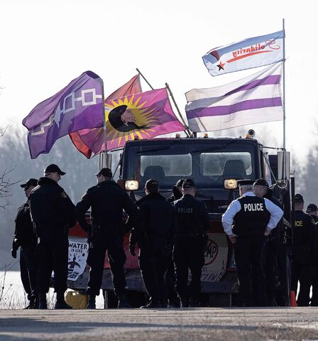 Ontario Provincial Police officers stand around the front of a barricade at a rail blockade in Tyendinaga Mohawk Territory, near Belleville, Ont., Monday. (Adrian Wyld / The Canadian Press)