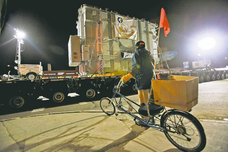 A cyclist is forced to wait for Manitoba Hydro's 320-tire unit to pass while it moves a transformer down Pembina Highway Sunday.