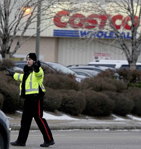 Members of the Winnipeg Police Service direct traffic in front of the St. James's Costco store in November. The Winnipeg Police Service says 481 off-duty officers have been hired so far this month to serve as armed paid security during the busiest shopping period of the year.