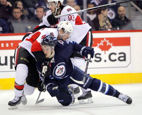 Mark Sheifele is brought down by Ottawa Senators' Patrick Wiercioch in second period action at the MTS Centre Wednesday. The Jets lost 3-1.