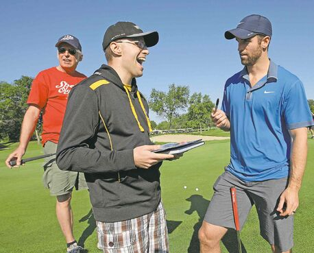 KEN GIGLIOTTI / WINNIPEG FREE PRESSAndrew Ladd (right) signs autograph for Special Olympan Philip Bialk and volunteer Ron Lambert (left) at Wednesday�s charity tournament.