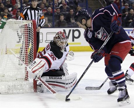 New Jersey Devils' Cory Schneider, left, makes a save against Columbus Blue Jackets' David Clarkson during the second period of an NHL hockey game Saturday, Feb. 28, 2015, in Columbus, Ohio. Clarkson will miss four to six weeks with a torn oblique muscle suffered Tuesday night against the Washington Capitals. THE CANADIAN PRESS/AP/Jay LaPrete