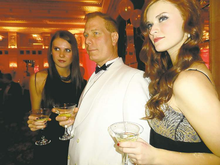 'James Bond' with a martini (played by Leon Alexander of Scheme-a-Dream) and two Bond Girls, one on each arm.