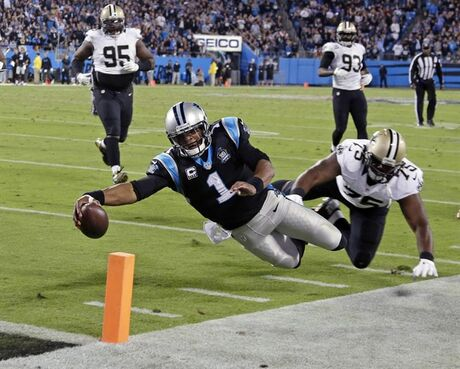 Carolina Panthers' Cam Newton (1) dives for the end zone for a touchdown as New Orleans Saints' Tyrunn Walker (75) defends in the second half of an NFL football game in Charlotte, N.C., Thursday, Oct. 30, 2014. (AP Photo/Bob Leverone)