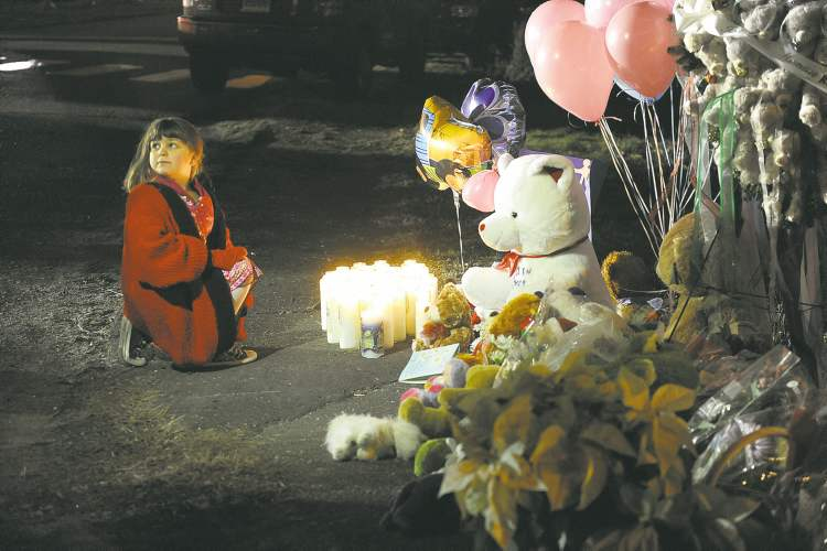 Olivier Douliery / MCT Candles are lit at a memorial near Sandy Hook Elementary School on Saturday in Newtown, Conn., a day after a shooting rampage at the school.