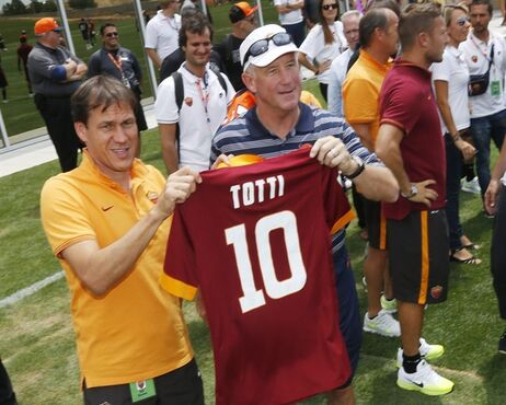 AS Roma manager Rudi Garcia, left, holds up a jersey with Denver Broncos head coach John Fox, center, as AS Roma player Francesco Totti, right foreground, joins teammates during photo session at the Broncos NFL football training camp in Englewood, Colo., on Friday, July 25, 2014. AS Roma team members were on hand to watch the Broncos in their second day of practice in preparation for the 2014 NFL season. AS Roma faces Manchester United in a game on Saturday in the Mile High City. (AP Photo)