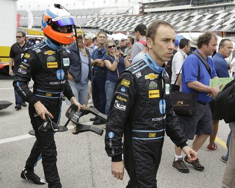 Co-drivers Jordan Taylor, left, and Max Angelelli, right front, of Italy, walk through the garage area during a practice session for the IMSA 24 hour auto race at Daytona International Speedway, Friday, Jan. 23, 2015, in Daytona Beach, Fla. (AP Photo/John Raoux)
