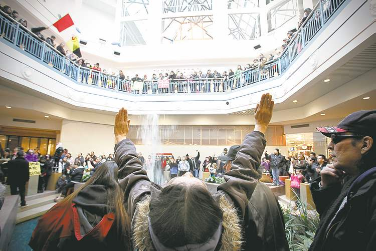 A woman raises her hands as hundreds of people take part in an Idle No More flash mob round dance at Portage Place Saturday, December 22. Idle No More is a national protest movement against the  impact of the federal government's omnibus budget bill.