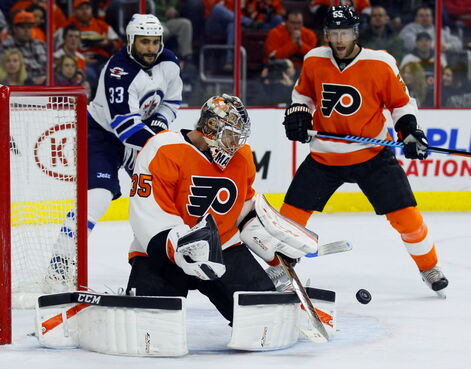 Philadelphia Flyers goalie Steve Mason (35) centre, makes a stick save on a shot as Winnipeg Jets' Dustin Byfuglien (33)  and Flyers' Nick Schultz (55) watch Thursday in Philadelphia.
