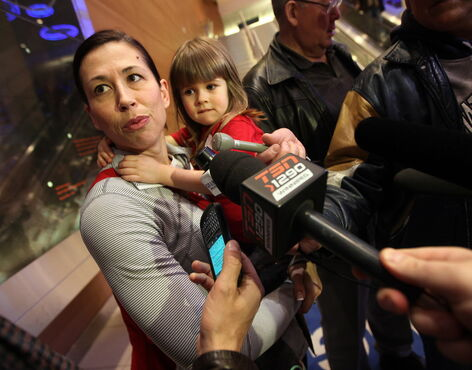 Team Canada's Jill Officer answers questions while holding daughter Camryn, 3, after arriving home from Japan with her silver championship medal.