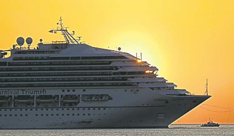 Dave Martin / The Associated PressThe Carnival Triumph is towed by a  tugboat into Mobile Bay, Ala., Thursday.