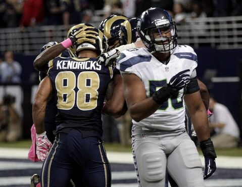 St. Louis Rams tight end Lance Kendricks, left, is congratulated after scoring on a 4-yard touchdown catch as Seattle Seahawks linebacker K.J. Wright, right, walks away during the fourth quarter of an NFL football game Sunday, Oct. 19, 2014, in St. Louis. The Rams won 28-26. (AP Photo/Tom Gannam)