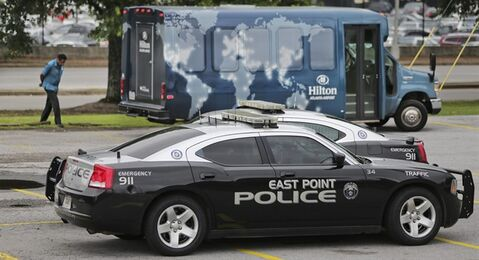 A driver walks outside his hotel shuttle bus, not involved in an accident, standing by, as East Point police complete their accident report inside their patrol cars near the scene of an accident, Thursday, June 12, 2014, in Fulton County, Ga. Authorities said several people were injured in a multi-vehicle wreck near Hartsfield-Jackson International Airport involving a hotel shuttle. (AP Photo/Atlanta Journal-Constitution, John Spink) MARIETTA DAILY OUT; GWINNETT DAILY POST OUT; LOCAL TV OUT; WXIA-TV OUT; WGCL-TV OUT.