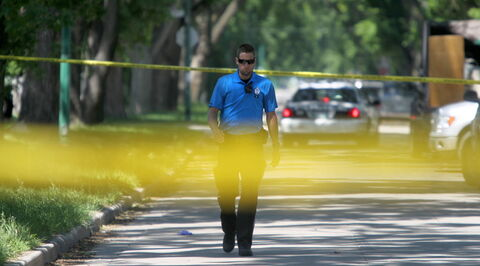 Police officers and cadets guard the scene of a stabbing  in the 400 block of Manitoba Ave. Saturday afternoon.