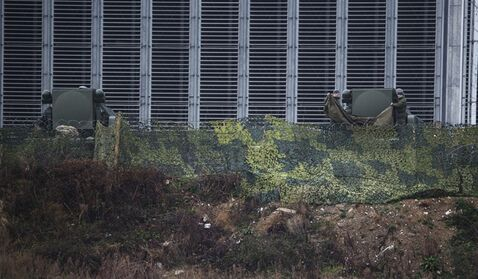 Russian soldiers fold a tarp in front of Tor-M1 air defense missile systems overlooking the Olympic Park ahead of the 2014 Winter Olympics, Wednesday, Jan. 29, 2014, in Sochi, Russia. The deployment of missiles is part of sweeping security measures put in place for the Olympics. (AP Photo/Pavel Golovkin)