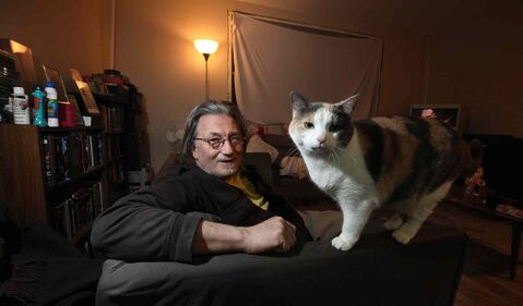 Formerly homeless, Alden Wiebe poses in the small Ellice Avenue apartment he shares with a partner and two cats. The building is being renovated around them.