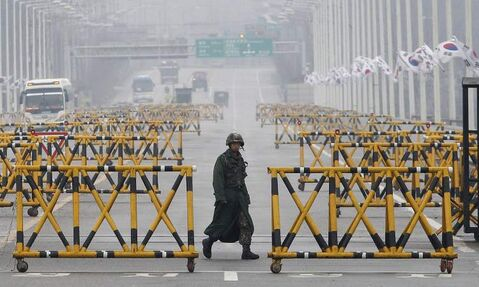 A South Korean Army soldier walks on Unification Bridge in Paju, South Korea, near the border village of Panmunjom, Saturday. More South Koreans on Saturday began to leave North Korea and the factory park where they work, four days after Pyongyang closed the border to people and goods.