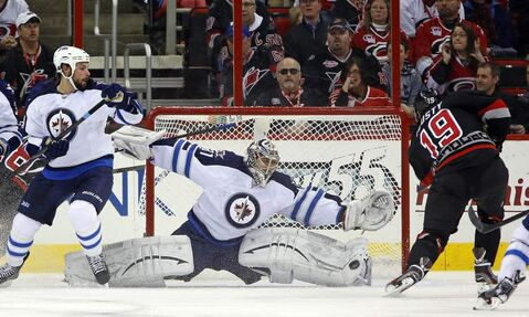 Carolina Hurricanes' Jiri Tlusty has his shot blocked by Winnipeg Jets goaltender Ondrej Pavelec as Jets defenceman Zach Bogosian defends during the first period of an NHL game in Raleigh, N.C., Tuesday.
