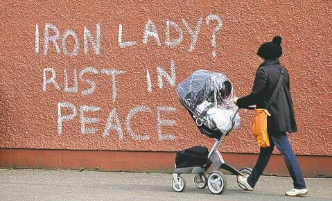 Anti-Thatcher graffiti adorns a wall in West Belfast, Northern Ireland.