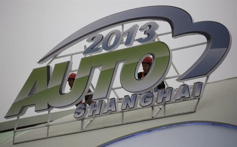 Workers install a sign ahead of the Shanghai International Automobile Industry Exhibition (AUTO Shanghai) at the Shanghai International Exhibition Center in Shanghai, China Thursday, April 18, 2013. THE CANADIAN PRESS/AP, Eugene Hoshiko