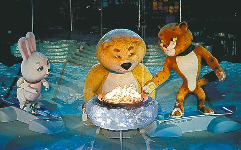 A large mascot gets ready to blow out the Olympic flame during the closing ceremony on Sunday.