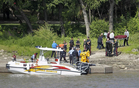 A body on a gurney is wheeled away from the riverbank on the Red River near Waterfront Drive Saturday.