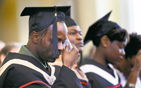 Samy Archille wipes away tears at the special convocation ceremony Friday morning.